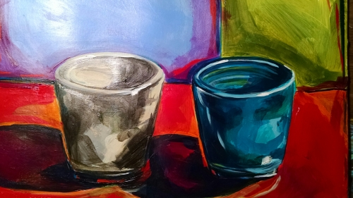 The image shows two cups - one gray one blue - on a red surface with two blocks of color, one pearly gray and one yellowy green behind them.