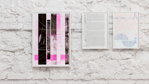 Image shows three prints in white frames on a white brick wall.
