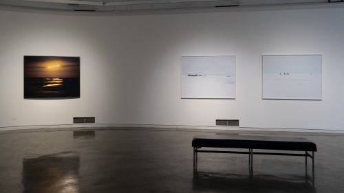 Two framed photos on a white wall, in front of them in a bench from the gallery.