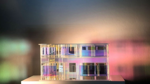 An acrylic model of the house Hahn grew up in bathed in different lights.