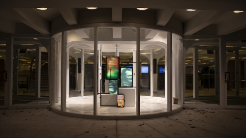 Image shows the Barrows Rotunda, a circular glass building with four screens showing different pixelated or blurred images in different colors rangind from orange to green-gray and five other empty frames.
