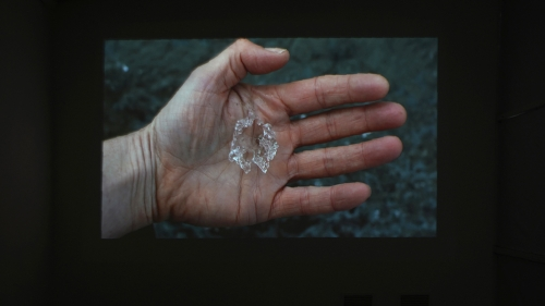 A still of a white hand with ice on the palm
