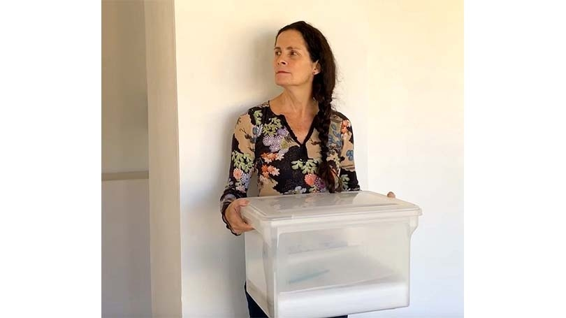 Brenda Garand holds a large plastic box in front of a white wall
