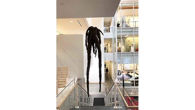 A sculpture, a body suspended supine, hanging in the stairwell of the Black Visual Arts Center