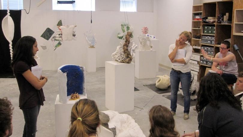Student critiquing work in a sculpture class