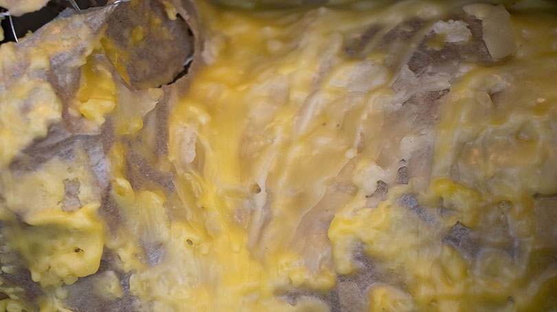 The image shows wax dripping in yellow splotches, an excerpt of the larger sculpture.