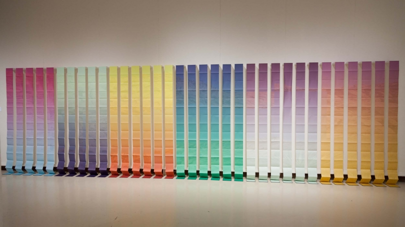 The image shows 33 accordian books in a wide gradient of colors (purples, blues, yellows, teal, violet, oranges) hanging from the wall with their book covers on the ground.