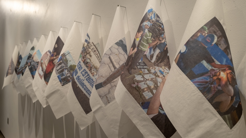 Images printed on white cloths, hanging in a line on a white wall.