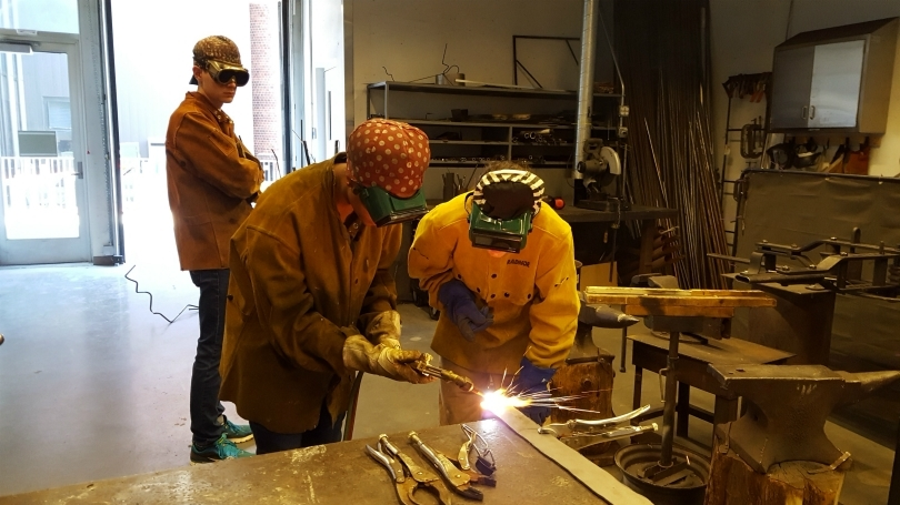Two students working on a welding project.